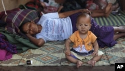 FILE - A baby sits next to her mother at a refugee camps in Laiza, an area controlled by the Kachin in northern Burma.