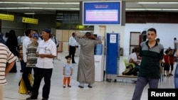 FILE - Passengers are seen in a hall at Tripoli's Mitiga International Airport.