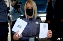 Seorang polisi wanita di perbatasan Bregana antara Kroasia dan Slovenia menunjukkan paspor digital COVID-19 Uni Eropa, 2 Juni 2021.