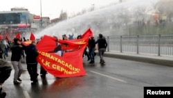 Protesters run from water cannons used by riot police to disperse them during a protest march to commemorate the death of Berkin Elvan, in Istanbul, March 11, 2015.