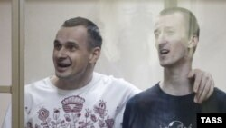 Oleg Sentsov (left) and Oleksandr Kolchenko behind glass in the courtroom.