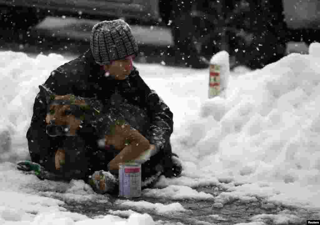 A man holds his dog as he begs on a street during a snowfall in Bucharest, Romania.