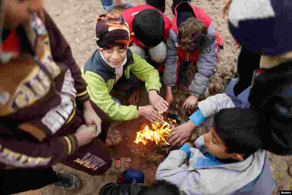 کودکان عراقی، که از دستداعش در موصل فرار کردند و در حال حاضر در اردوگاهی در عراق زندگی میکنند، در کنار آتش دستهای خود را گرم میکنند.