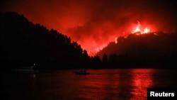 Api kebakaran hutan berkobar di Limni, Pulau Evia, Yunani, 6 Agustus 2021. (Foto: Sotiris Dimitropoulos/Eurokinissi via Reuters