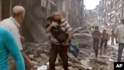 A man carries a child after airstrikes hit Aleppo, Syria. (April 28, 2016)