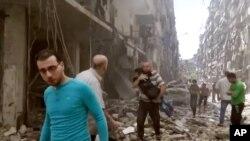 Trẻ em được đưa ra khỏi hiện trường sau một vụ không kích ở Aleppo, Syria.