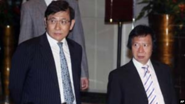 Sun Hung Kai Properties Joint Vice Chairmen and Managing Directors, Raymond and Thomas Kwok, walk outside their business headquarters in Hong Kong, April 3, 2012.