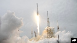 FILE - A rocket carrying the SpaceX Dragon ship lifts off from launch complex 40 at the Cape Canaveral Air Force Station in Cape Canaveral, Florida, April 18, 2014.