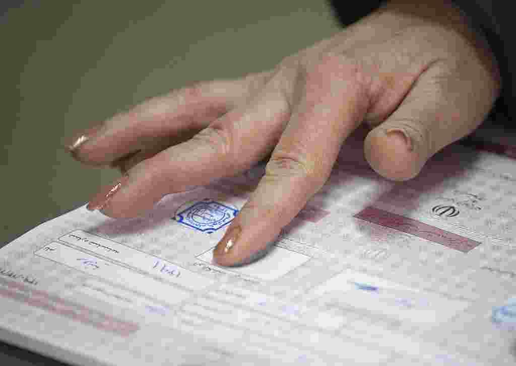La impresión digital de una mujer marca el momento de la identificación para el voto en Teherán.