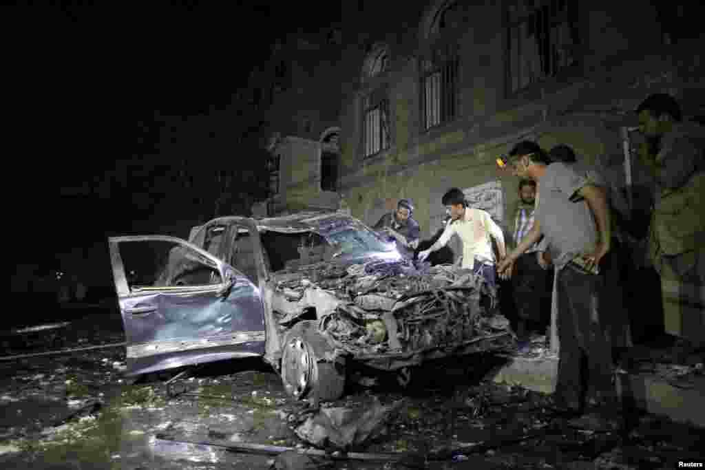 Orang-orang memeriksa mobil yang rusak akibat ledakan bom dekat sebuah masjid di ibukota Yaman, Sana'a. Dua ledakan bom yang mematikan terjadi di ibukota dan di kota selatan, menurut kantor berita Saba, sehari setelah serangan udara dan bentrokan menewaskan hampir 200 orang di seluruh penjuru negeri.