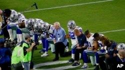 Dalas Kaubojs, predvođeni vlasnikom Džerijem Džonson, kleče pred početak NFL utakmice protiv Arizona Kardinalsa.