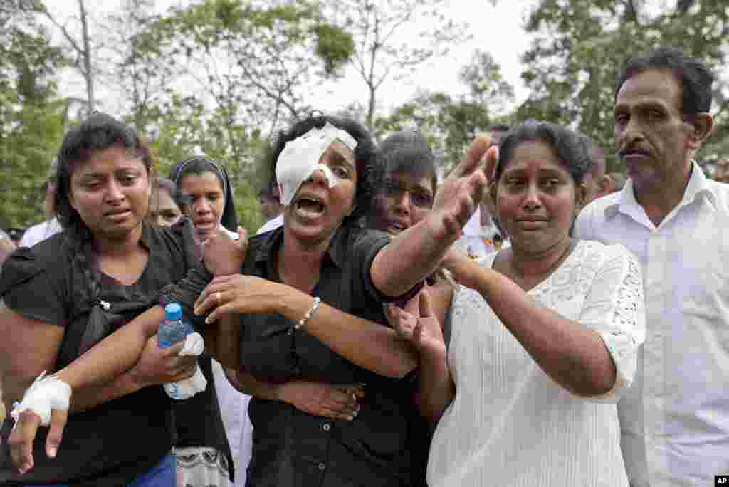 Anusha Kumari, center, weeps during a mass burial for her husband, two children and three siblings, all victims of Easter Sunday's bomb attacks, in Negombo, Sri Lanka.