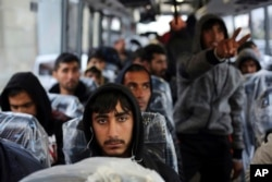 """Migrants sit on a bus going to Normandy, as they leave the makeshift migrant camp known as """"the jungle"""" near Calais, northern France, Oct. 24, 2016."""