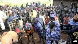 People gather around teenage girls from Uganda's Sebei tribe who have just undergone female genital mutilation near Kampala, Feb. 2011 (file photo).