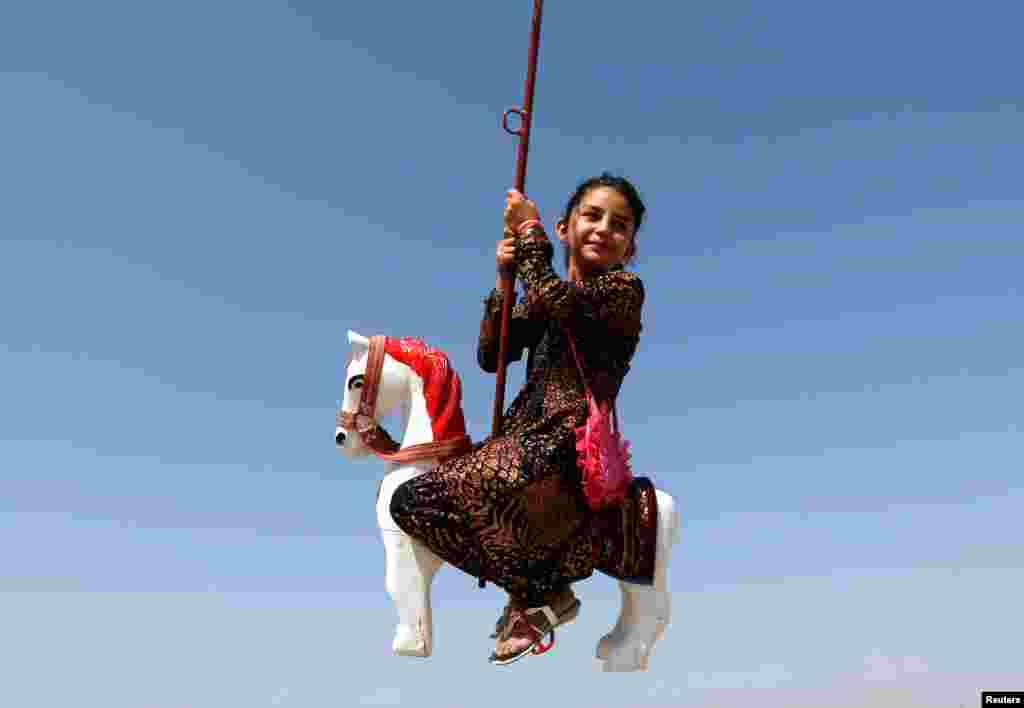 دخترک افغان در حال سواری بر اسپ مصنوعی در روز اول عید اضحی در کابل.