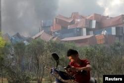 Seorang pria memeriksa ponselnya dekat kontainer pengapalan yang terbalik akibat dua ledakan besar di distrik Bihai, Tianjin, China (13/8).