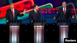 Presidential candidate Donald Trump (L) responds to criticism from former Governor Jeb Bush (R) as Senator Ted Cruz (C) looks on during the Republican presidential debate in Las Vegas.