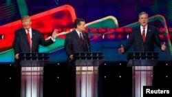 ڈونلڈ ٹرمپ (بائیں) جیب بش (دائیں) کی تنقید پر ہنس رہے ہیں جبکہ ٹیڈ کروز (درمیان) انہیں دیکھ رہے ہیں۔