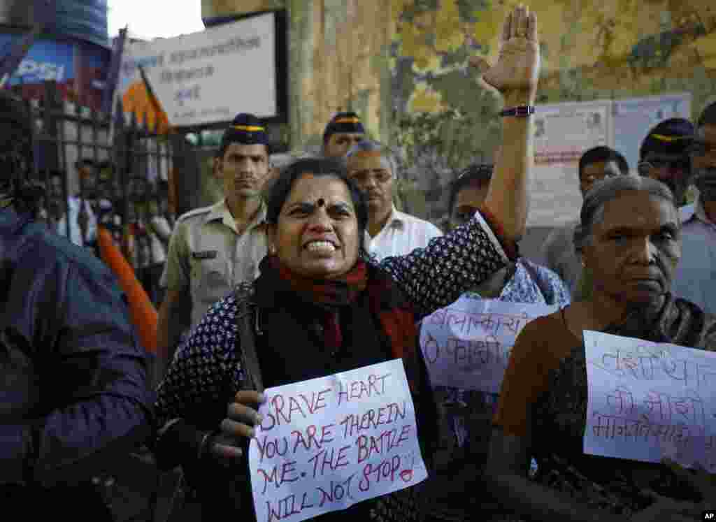 An Indian woman shouts at a police officer during a gathering of people to mourn the death of the 23-year-old gang rape victim in Mumbai, Saturday, Dec. 29, 2012.