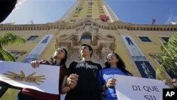 来自阿根廷的非法移民帕谢罗(中),他的母亲萨沙(右)以及他的女友,一名移民问题活动人士莫拉加(左)在迈阿密市中心的自由塔前举着标语