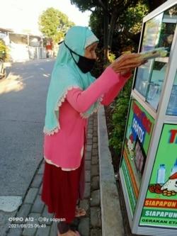 Seorang ibu mengambil nasi gratis. (Foto: Courtesy)