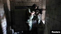 A Free Syrian Army fighter aims his weapon as he takes position inside a house in the city of Aleppo July 11, 2013.