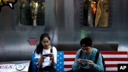 FILE - Shoppers sit on a bench with a decorated U.S. flag browsing their smartphones outside a fashion boutique selling U.S.-brand clothing at the capital's popular shopping mall in Beijing, Sept. 24, 2018.