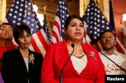 FILE - Immigration activist Astrid Silva (in red) stands next to her mother, Barbara Silva, as she speaks about immigration reform at a news conference on Capitol Hill in Washington, Dec. 10, 2014. Astrid Silva will be one of the speakers on the opening night of the 2016 Democratic National Convention.
