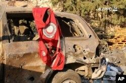 This image provided by the Syrian anti-government group Aleppo 24 news, shows a vest of the Syrian Arab Red Crescent hanging on a damaged vehicle, in Aleppo, Syria, Sept. 20, 2016.