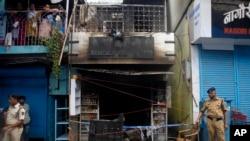 Polisi India berdiri di depan apotek yang terbakar di Mumbai, India (30/6).