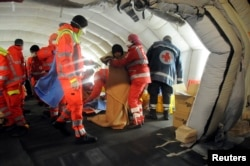 Medics help migrants in a tent after they arrived onboard the Blue Sky M cargo ship at the Gallipoli harbor, southern Italy, Dec. 31, 2014.