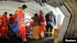 Para petugas medis membantu para migran penumpang kapal Blue Sky saat mendarat di Gallipoli, Italia (31/12).