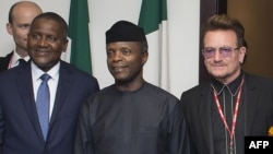Nigerian Vice President Yemi Osinbajo (C) flanked by Africa's richest man, Aliko Dangote, (L) and international rock star Bono meet in Abuja, Aug. 29, 2016.