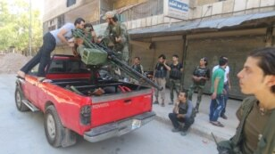 FILE - Free Syrian Army fighters inspect a pick-up truck with a weapon installed on it as they gather during what they said was an operation to travel to the northern countryside of Aleppo to fight Islamic State fighters, in Aleppo, Syria.