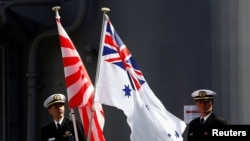 Crew members from the Japanese Maritime Self-Defense force ship Umigiri stand on deck between Japan's Self-Defense Force flag alongside an Australian flag before joint exercises at Garden Island Naval Base in Sydney, April 19, 2016.