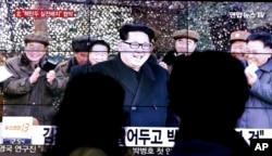 ຜູ້ຄົນຢ່າງຜ່ານໂທລະພາບ ທີ່ເຫັນຮູບຂອງທ່ານ Kim Jong Un ໃນ ເກົາຫລີໃຕ້ .