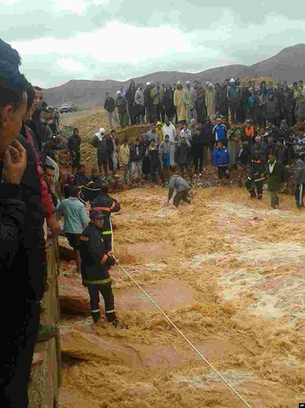 Cette image prise avec un téléphone portable montre pompiers marocains tirant une corde dans une tentative de sauver les habitants de Guelmim, au sud ouest du Maroc, bloqués par la crue des eaux, lundi 24 novembre 2014.