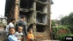 Anak-anak Nepal berdiri di depan bangunan yang runtuh akibat gempa yang mengguncang Katmadu, Nepal, India (19/9).Anak-anak Nepal berdiri di depan bangunan yang runtuh akibat gempa yang mengguncang Katmadu, Nepal, India (19/9).