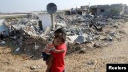 이스라엘과 팔레스타인 무장단체 하마스가 13일 72시간 휴전 만료를 앞둔 가운데, 가자지구 남부 지역의 한 팔레스타인 소년이 동생을 안고 폐허가 된 마을을 지나고 있다.