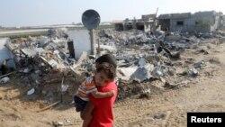 Trong đợt ngừng bắn 72 giờ, một cậu bé người Palestine bế em trai mình đứng cạnh căn nhà của mình đã bị phá hủy trong đợt tấn công của Israel, 13/8/2014.