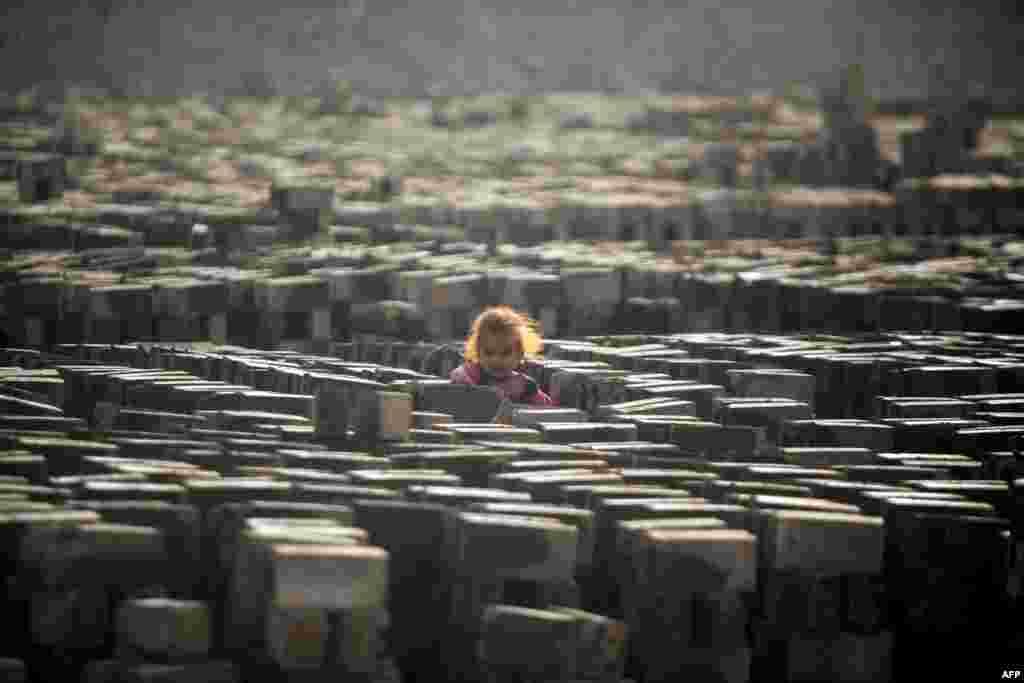Seorang anak perempuan berdiri di antara batu-bata yang dikeringkan di sebuah pabrik batu-bata dekat kota Najaf, Irak.