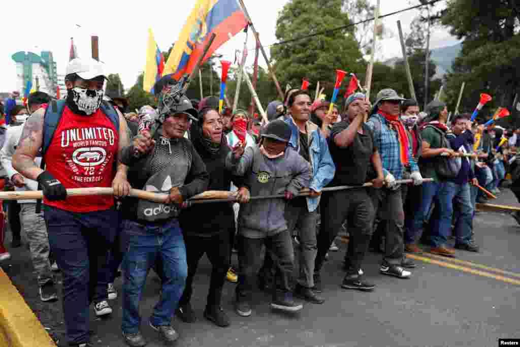 Manifestantes hacen una barrera humana ayudados por maderos en las calles de Quito, Ecuador. Octubre 8, 2019. REUTERS/Carlos Garcia Rawlins.