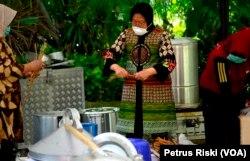 Wali Kota Surabaya Tri Rismaharini terlibat dalam aktivitas penyediaan minuman dan makanan tambahan di dapur umum. (Foto: VOA/Petrus Riski)