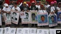 Kerabat dari 43 siswa sekolah guru yang hilang memegang poster dengan foto-foto orang-orang yang mereka cintai dalam aksi protes memperingati lima tahun menghilangnya para siswa tersebut, di Mexico City, Kamis, 26 September 2019.