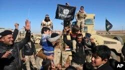 이라크 정부군이 24일 ISIL로부터 모술 동부 지역을 재탈환한 가운데, ISIL 깃발을 거꾸로 들고 주민들과 함께 기뻐하고 있다.