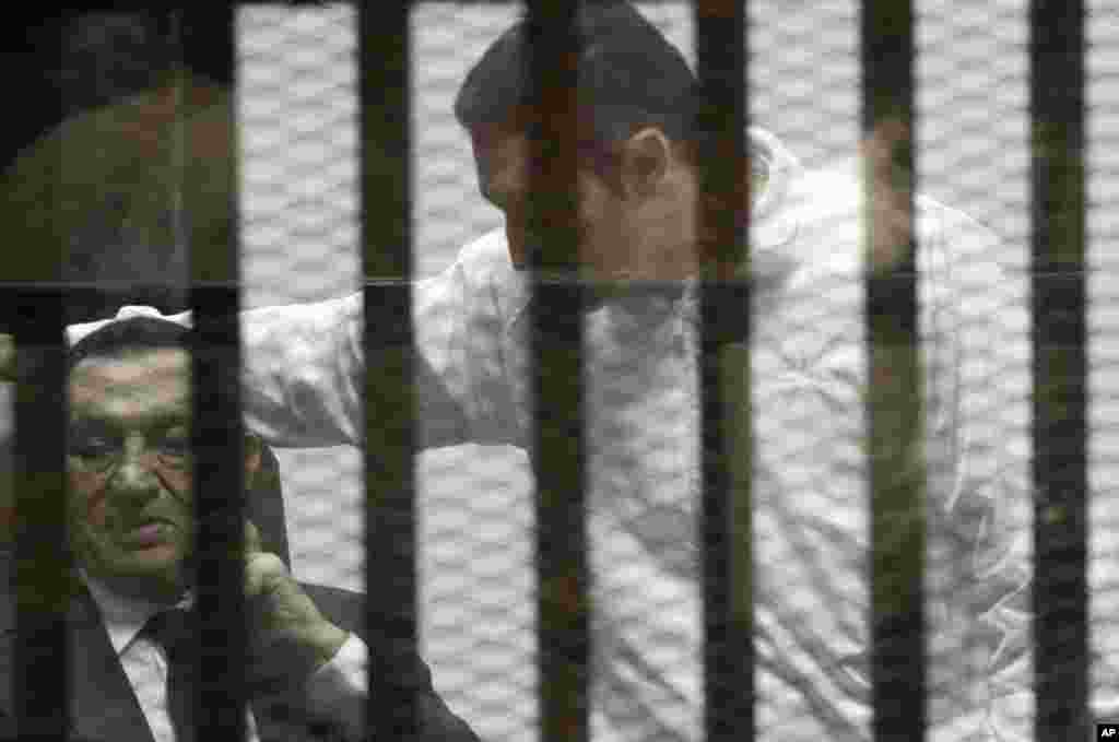 Ousted Egyptian president Hosni Mubarak, sits in a defendant cage with protective glass along side his son Alaa (right) during a court hearing in Cairo, May 21, 2014.