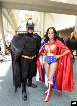 Pasangan suami istri Ken dan Michelle Camarillo, sebagai Batman dan Wonder Woman costumes, berpose pada hari kedua Comic-Con International 2015 di San Diego Convention Center, 10 Juli 2015, di San Diego.