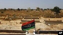 ທຸງຂອງພວກກະບົດປິວຢູ່ເໜືອຂຸມຝັງສົບຂອງນັກລົບຄົນນຶ່ງຂອງຝ່າຍກະບົດ ທີ່ເສຍຊີວິດໄປໃນການຕໍ່ສູ້ກັບກໍາລັງ ຂອງກາດດາຟີ ທີ່ເມືອງ Benghazi ທີ່ຢູ່ໃຕ້ການຄວບຄຸມຂອງພວກກະບົດ, ວັນທີ 17 ກໍລະກົດ 2011 ນີ້.