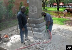 FILE - Workers begin removing a Confederate statue in Gainesivlle, Fla., Aug. 14, 2017. The statue is being returned to the local chapter of the United Daughters of the Confederacy, which erected the bronze statue in 1904.