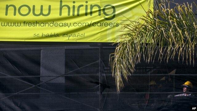 Un trabajador de la construcción junto a un letrero que anuncia nuevas contrataciones en Los Angeles.